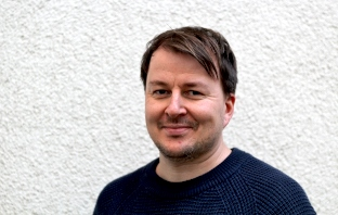 Porträtbild von Andreas Becker vor weißer Wand