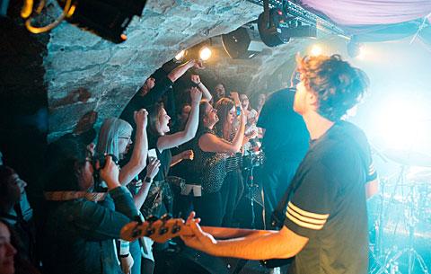 Band spielt auf der Bühne, Publikum jubelt